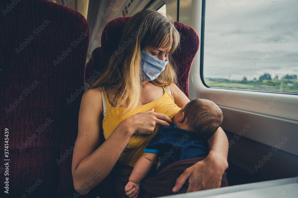 Fototapeta Mother with face mask breastfeeding baby on train