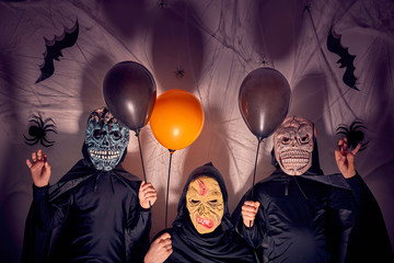 Two 7 years old boys with their mother in halloween costumes with masks as monsters and a witch holding black and orange balloons. Dark background with shadows, spiders, spiderwebs and bats.