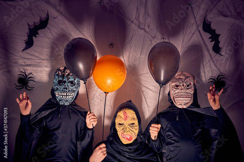 Valokuva Two 7 years old boys with their mother in halloween costumes with masks as monsters and a witch holding black and orange balloons
