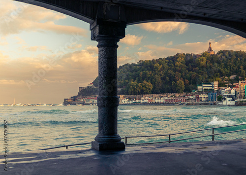 Fotomural first lights of day in the arcades of la cocha beach in san sebastian, spain
