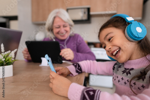 Photo Joyful brazilian young child with headphone enjoying music and looking at smart cell phone screen in kitchen home, indoors