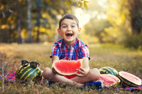 Fotografie, Obraz happy boy eating ripe watermelon in summer park