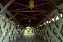 Inside View Of Covered Bridge In Madison County, Winterset, Iowa, With Trusses, Running Boards, Yellow Lights, And Light At The End Of The Tunnel  Royalty Free Stock Photo
