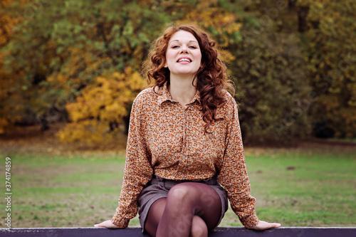 jeune et jolie femme rousse dans un parc arboré en automne avec des feuilles mor Canvas Print