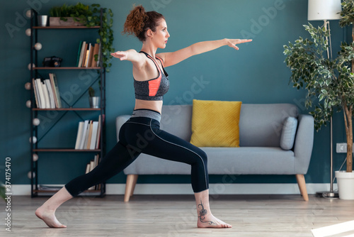 Obraz na plátně Attractive sporty young woman doing hypopressive exercises in living room at home