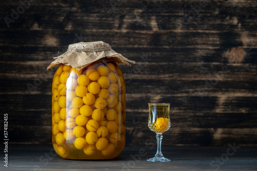 Fotografija Homemade tincture of yellow cherry plum in glass jar and a wine crystal glass on