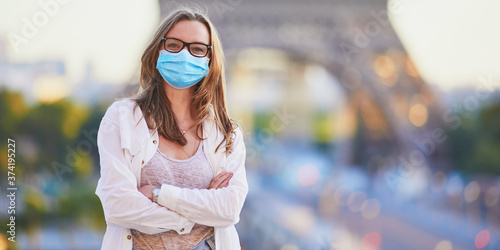 Papel de parede Girl standing near the Eiffel tower in Paris and wearing protective face mask du