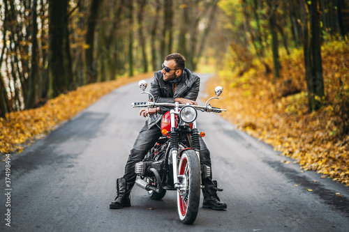 Bearded brutal man in sunglasses and leather jacket sitting on a motorcycle on t Canvas Print