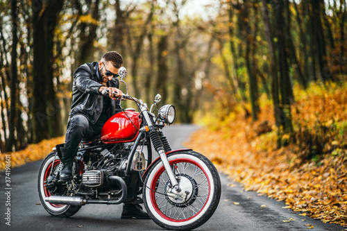 Foto Bearded brutal man in sunglasses and leather jacket sitting on a motorcycle on t