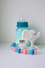 Large Silicone Clip For Baby Pacifier And Milk Bottle On White Background. Soft Toy In The Form Of An Elephant. Beautiful Accessories For A Newborn. The Concept Of Happy Motherhood And Childhood.