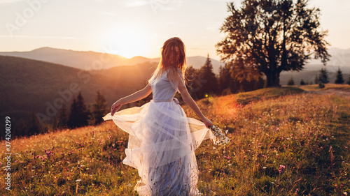 Canvastavla Beautiful bride dancing in blue wedding dress in mountains at sunset