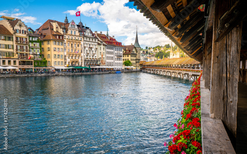Scenic view of Lucerne old town with flowers along Chapel bridge with colorful h Fotobehang