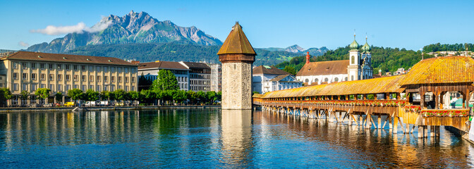 Scenic panoramic view of Lucerne with Chapel bridge or Kapellbrucke and Pilatus mount with clear blue sky during summer Lucerne old town Switzerland