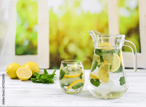 lemonade with lemon and mint. Lemonade with lemon and mint in a jug and in a glass stand diagonally on a wooden window sill against the background of an open window, close-up side view.