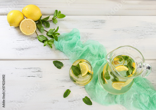 lemonade with lemon and mint. Lemonade with lemon and mint in a jug and in a glass stands diagonally on a wooden white table, close-up top view.