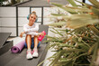 Young woman sitting and resting after workout or exercise in fitness gym with protein shake or drinking water and listen the music. Rolled yoga mat lie next to her.  Relax concept, healthy lifestyle