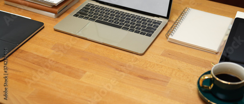 Photo Workplace with copy space, laptop, supplies, stationery and coffee cup on wooden