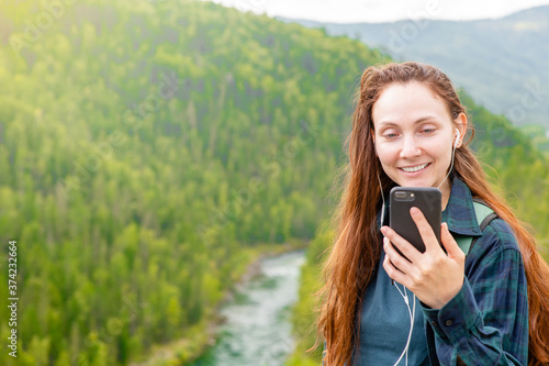 Photo Smiling woman wearing headphones holds smartphone at mountains and listening to