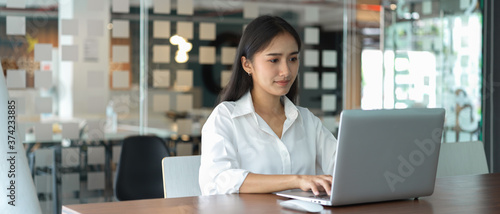 Obraz na plátně Portrait of female office worker working with laptop in glass partition room