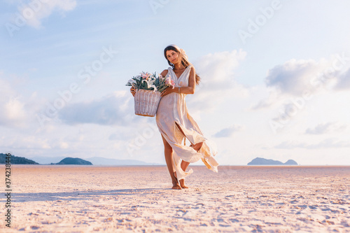Fotografija beautiful young stylish woman with basket with flowers outdoors at sunset