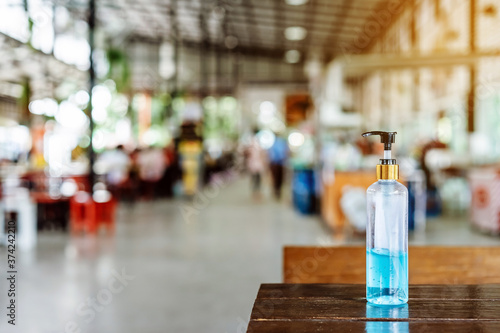 Obraz Blue alcohol gel bottle for hand cleaning to prevent the spreading of the Coronavirus (Covid-19) to service for customers placed on table at cafeteria. Healthcare concept. New normal lifestyle - fototapety do salonu