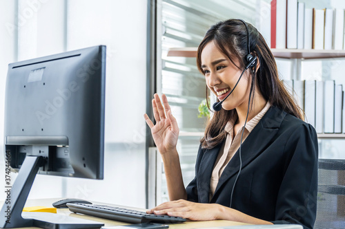 Smiling friendly asian businesswoman with headset working and greets interlocutor for online communication Canvas Print