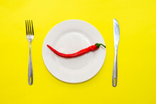 Red Chili Pepper On White Plate With Fork And Knife On Yellow Background Top View. Hot News Concept.