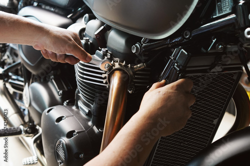 Fotografía Mechanic using a wrench and socket on exhaust pipe of a motorcycle