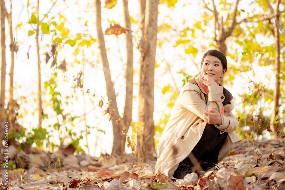 Fototapeta 秋の自然の中にいる女性のイメージ