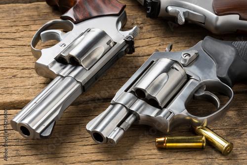 Fototapeta Revolver guns and bullets on wooden background