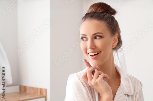 Obraz Beautiful young woman with lipstick at home - fototapety do salonu