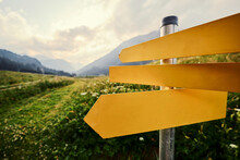 Yellow Empty Signboard With Pointer Against Beautiful Mountains Landscape, Tirol Alps, Austria.