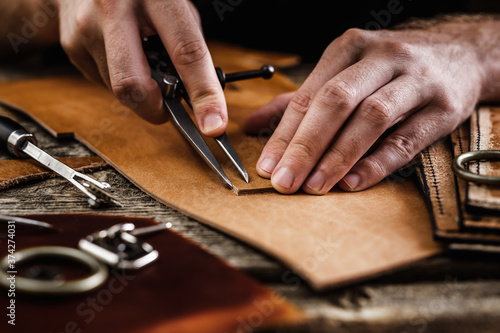 Obraz Close up of a shoemaker or artisan worker hands. Leather craft tools on old wood table. Leather craft workshop. - fototapety do salonu