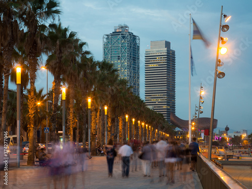 Fotografie, Obraz Illuminated quay next to Barceloneta beach in Barcelona with blurred people