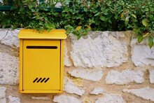 Beautiful Yellow Post Letter-box On The Stone Wall Outdoors.
