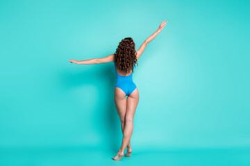 Rear back view photo slim alluring young lady perfect shape curly hairstyle make hand dance move comfort beach outfit advert concept wear blue swimsuit isolated turquoise color bakground