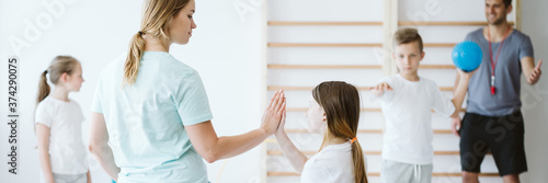 Obraz Girl doing high five with her teacher during physical education - fototapety do salonu