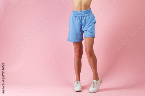 Photo Beautiful long woman legs in shorts and white sneakers posing in studio fashion