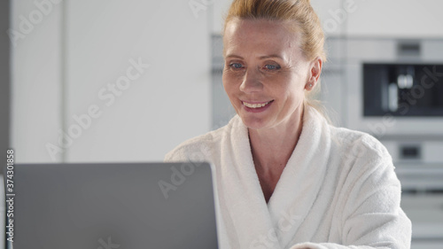 Obraz na płótnie Portrait of mature woman in bathrobe surfing internet on laptop at home
