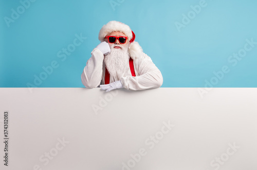 Portrait of his he nice attractive bored sad white-haired Santa presenting copy space board advice look idea solution promotion isolated over bright vivid shine vibrant blue color background