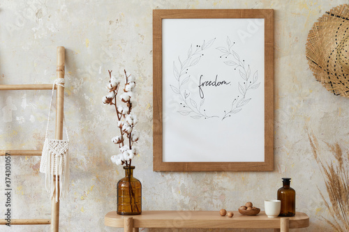 Obraz na plátně Beige boho interior of living room with mock up poster frame, elegant accessories, dried flowers in vase, wooden console and hanging rattan hut in stylish home decor