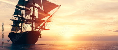 Fotografiet Pirate ship sailing on the ocean at sunset