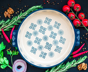 Round food frame with blue dish, chilli, cherry tomatoes, spices with copy space