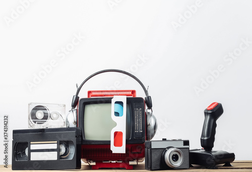 Photo Retro portable mini tv set with headphones, 3d glasses, camera, joystick, audio and video cassette on white background