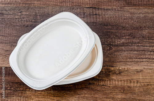 Biodegradable dish on wooden background.