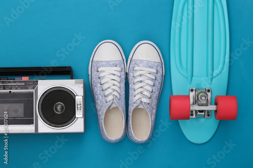 Fotografie, Obraz 80s Retro outdated portable stereo radio cassette recorder with cruiser board, sneakers on blue background