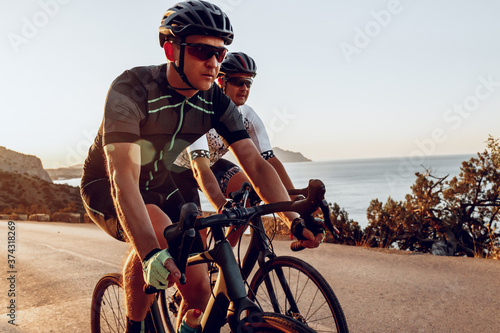 Two professional male cyclists riding their racing bicycles in the morning toget Wallpaper Mural