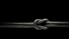 Reef Knot Black Rope On A Black Background.