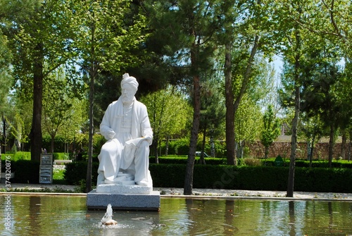 Obraz na plátně The statue of 10th century Persian poet Ferdowsi, surrounded by tall trees and water stream