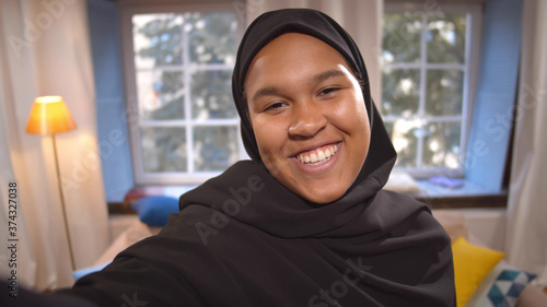 Fotografie, Obraz Young muslim woman in hijab talking on video call or filming for internet blog